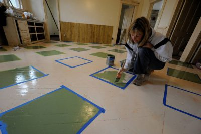 Photo: A woman paints a pattern on the kitchen floor of a farmhouse near Dunbar, Nebraska.