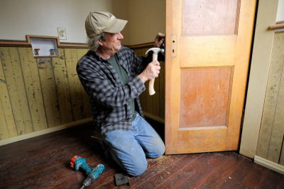 Photo: A carpenter repairs and hangs a door at a farmhouse near Dunbar, Nebraska.