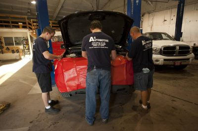 Photo: Three mechanics tackle an engine problem