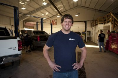 Photo: The owner of an auto shop stands proudly in his garage.