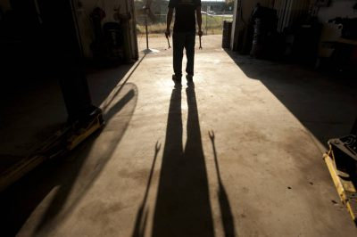 Photo: A mechanic's shadow stretches out before him.