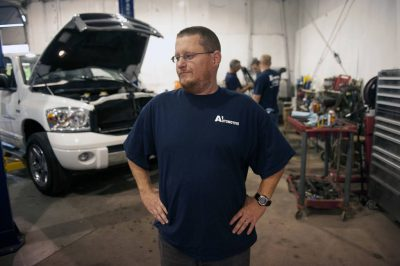 Photo: A mechanic stands inside an auto shop.