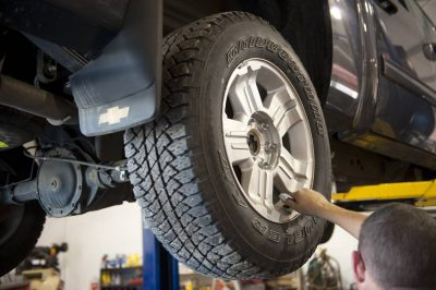 Photo: A mechanic removes a truck tire at an auto shop.