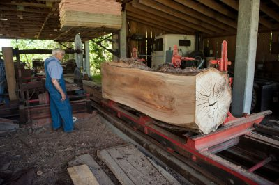 Photo: A man uses a sawmill to cut a log into boards.