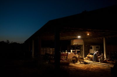 Photo: Two men work late at a sawmill.
