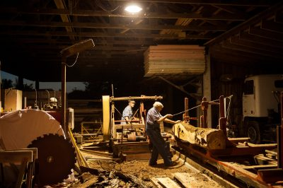 Photo: Two men hard at work at a sawmill.