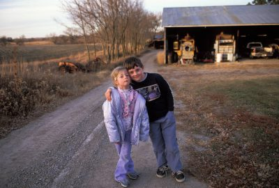 Photo: A young brother and sister hug on a gravel road in rural Nebraska.