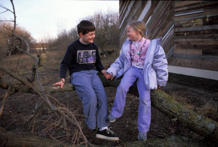 Photo: A young brother and sister hold hands on a gravel road in rural Nebraska.