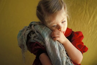 Photo: A young girl sucks her thumbs while hanging on tight to her blanket.
