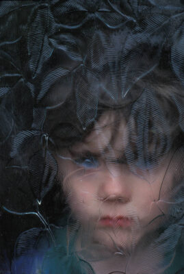 Photo: A young boy's face is shown through a patterned window.