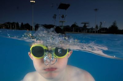 Photo: A boy goes for a swim in a local neighborhood pool.