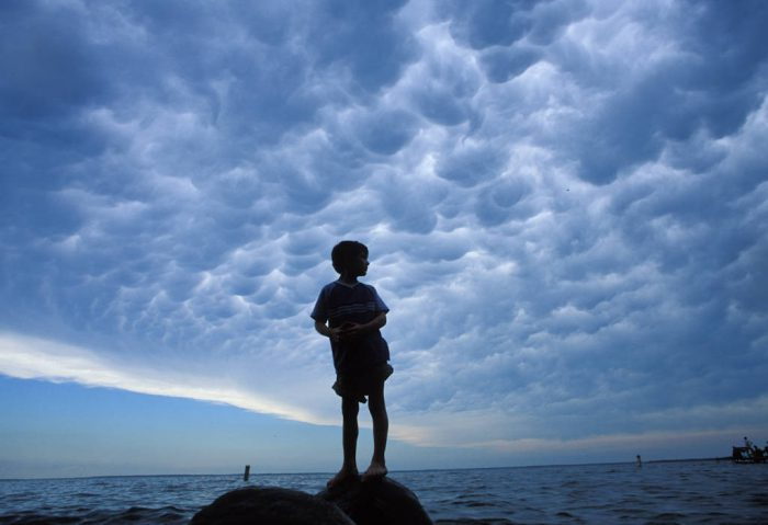 Photo: A young boy stands on a rock in the middle of a lake.