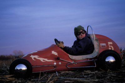 "Photo: A boy in a ""midget racer."""