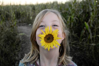 Photo: A young girl plays with a sunflower at a pumpkin patch near Roca, NE.
