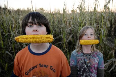 Photo: Kids pretend to eat corn cobs at a pumpkin patch near Roca, NE.