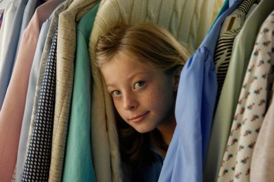 Photo: A 10-year-old girl plays in a rack of clothes at her grandmother's house.