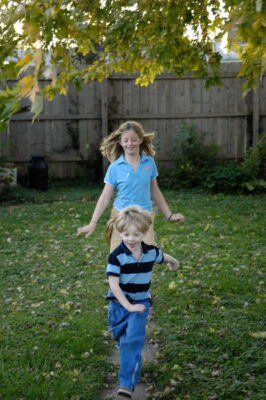 Photo: A brother and sister play together in a backyard.