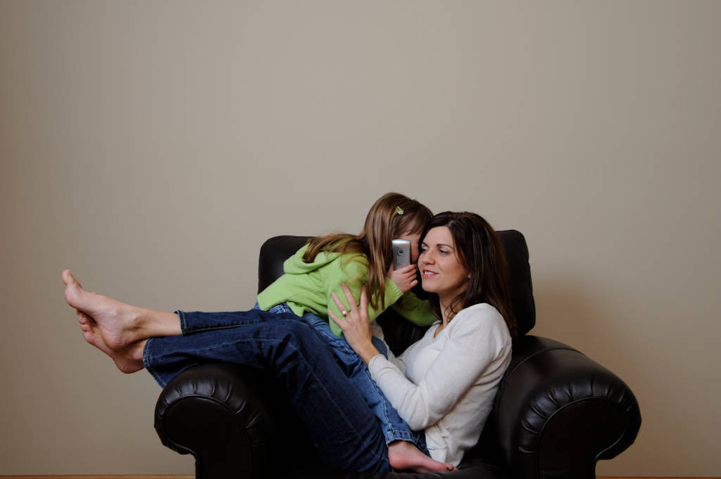 Photo: A 6-year-old and her mother talk on a celllular telephone.