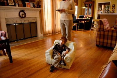 Photo: A 3-year-old boy watches TV in his child-size armchair.