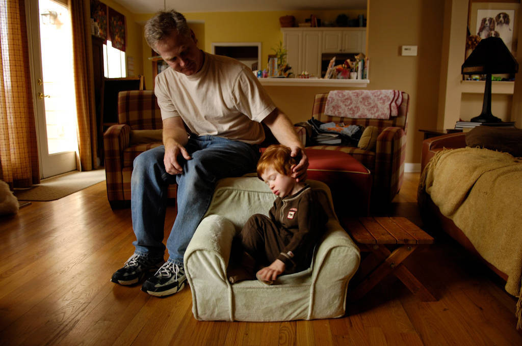 Photo: A 3-year-old boy curls up in his child-size armchair.