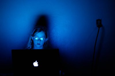Photo: A 10-year-old girl works on a computer in a dark room.