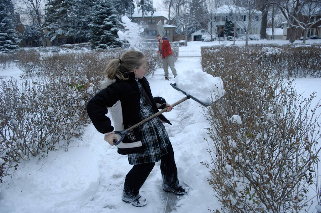 Photo: A girl and her brother shovel snow from a sidewalk.