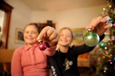 Photo: Two young girls hang ornaments on a tree.