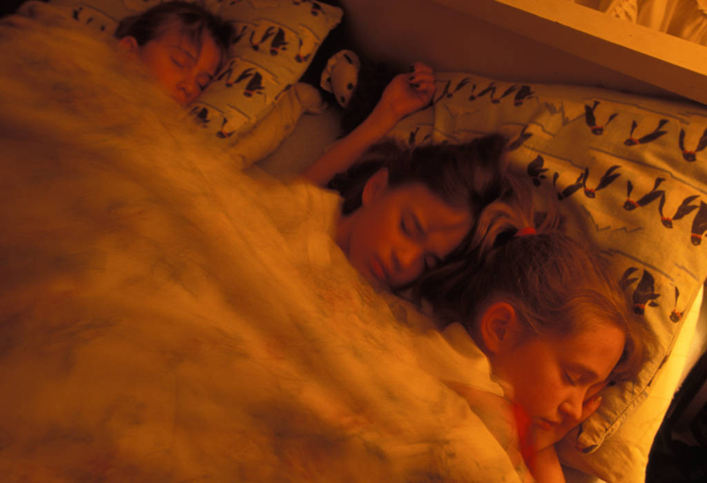 Photo: Three young girls take a nap.