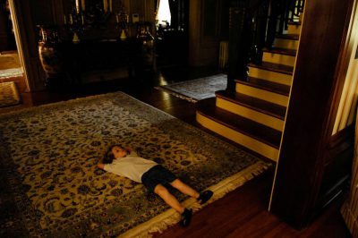 Photo: A young boy takes a nap at the foot of a staircase.
