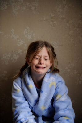 Photo: A 10-year-old girl cries in her pajamas.