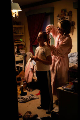 Photo: A woman fixes the hair of her ten-year-old daughter before school.