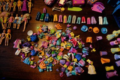 Photo: Many Polly Pockets dolls arranged on top of a table.