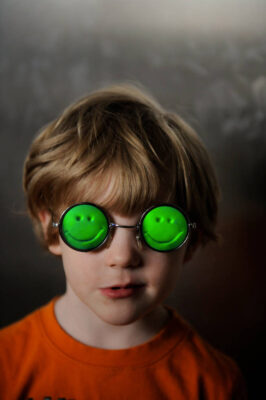 Photo: A young boy wear smiley face sunglasses.