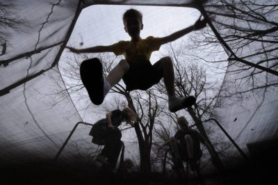 Photo: Kids jump on a trampoline as seen from underneath.