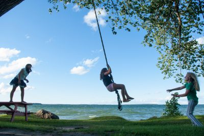 Photo: Three girls play on a rope swing along the shores of Leech Lake, MN.