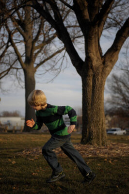 Photo: A young boy plays outside the Nebraska state capitol building.