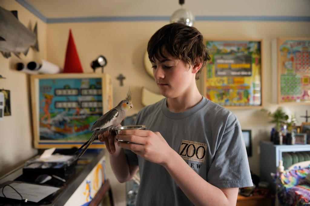 Photo: A teenage boy with his pet cockatiel.