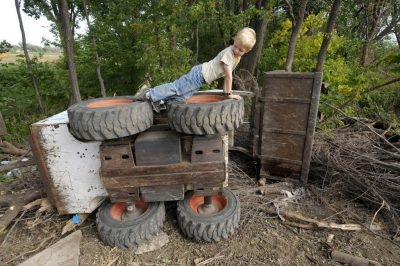 Photo: A boy plays on an overturned Bobcat.