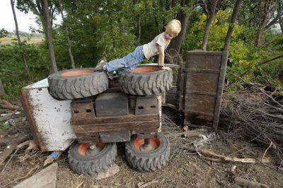 Photo: A boy plays on an overturned Bobcat.