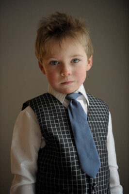 Photo: Portrait of a young boy in dress clothes.