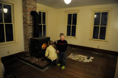 Photo: A brother and sister warm up next to a wood stove in a Nebraska farm house.