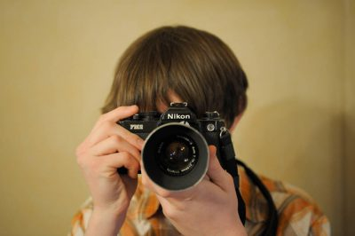 Photo: A boy uses a Nikon FM-2 camera.