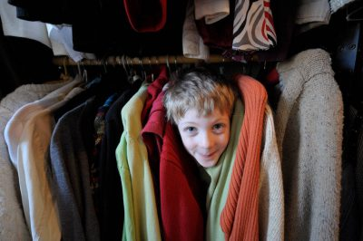 Photo: A boy peeks between shirts in a clothes closet.