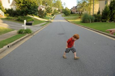 Photo: A five year-old boy plays in the street near his home.