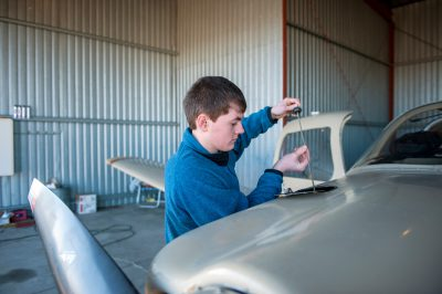Photo: A teenage boy checks the oil in a single engine aircraft before taking it for a student flight in Lincoln, Nebraska.