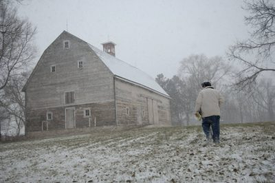 Photo: A man braves a snowstorm while approaching an old farmhouse.