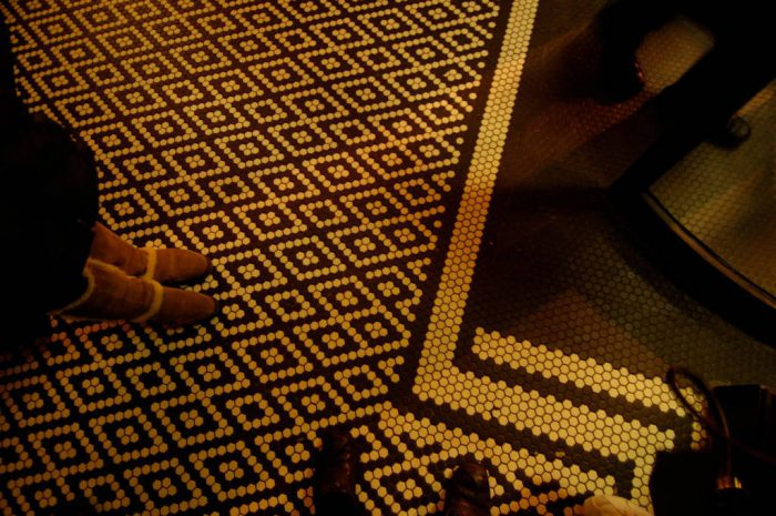 Photo: A woman stands on a tiled floor on Staten Island, New York.