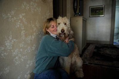 Photo: A woman hugs her fanci doodle dog.