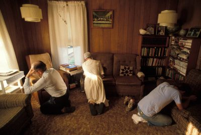 Photo: A Mennonite family prays in their home in Partridge, KS.