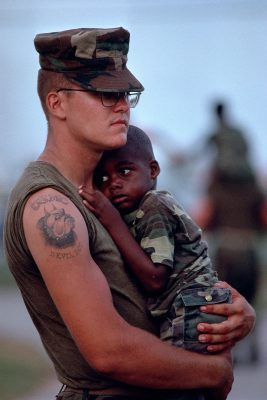 Photo: A Marine soldier cradles a little boy in a Florida city relief camp after hurricane Andrew.